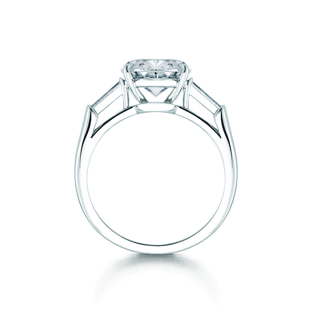 A Classic Diamond Ring In Platinum With An Oval Diamond Center Stone  Accented By A Tapered Baguette Diamond On Each Side I Love The Knotted  Accents On The